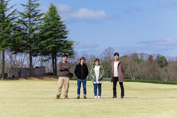4人が外の芝生に立っている